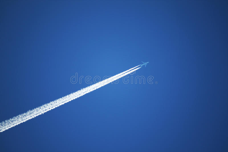 Jet Airplane Streams In The Sky Stock Photo