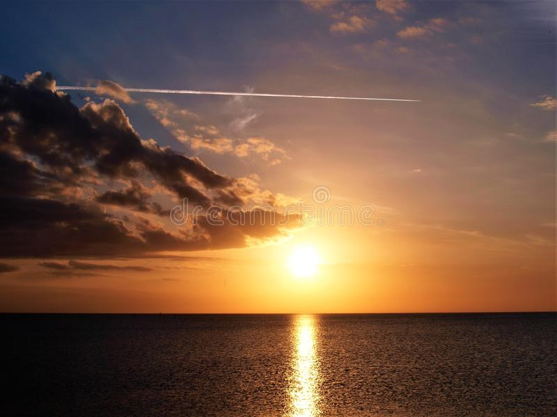 Jet Contrail sobre o por do sol de Okeechobee do lago foto de stock royalty free