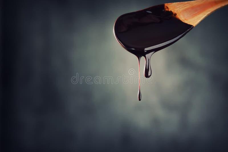 Jet der heißen Schokolade tropft vom hölzernen Löffel auf dunklem Hintergrund stockfoto
