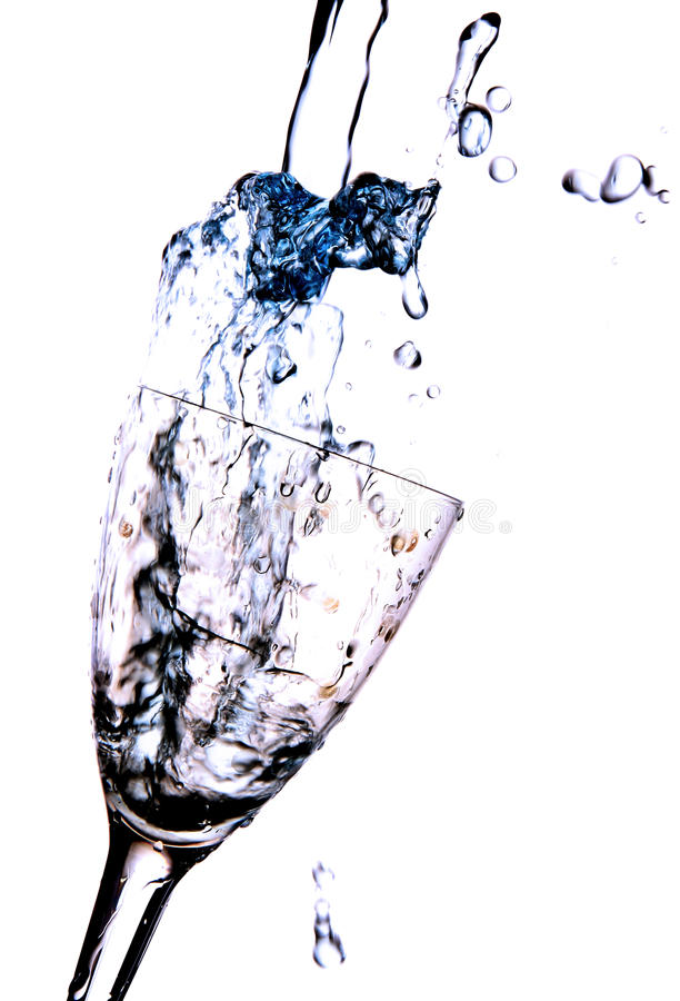 Drink pouring into glass. Jet drink in the glass creates a splash and spray, photo on white background royalty free stock image