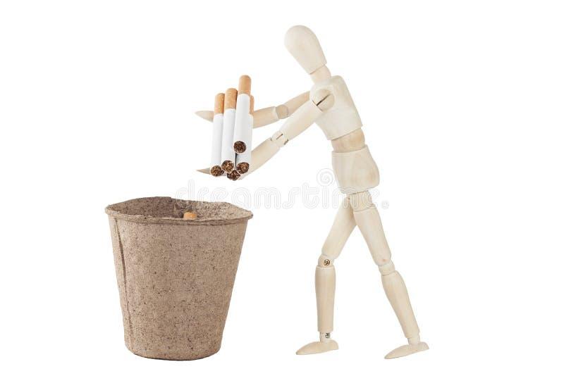 Jet en bois de mannequin dans les déchets quelques cigarettes photo libre de droits