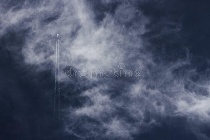 Jet en dampslepen die rechtstreeks over een bewolkte diepe blauwe hemel stijgen stock afbeeldingen