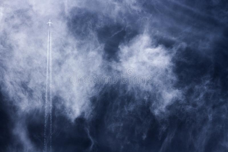 Jet en dampslepen die rechtstreeks over een bewolkte diepe blauwe verdonkerende hemel stijgen royalty-vrije stock foto's