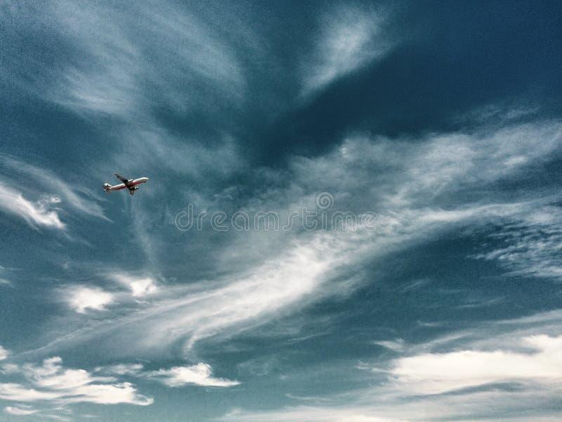 Jet en un cielo del cirro fotografía de archivo