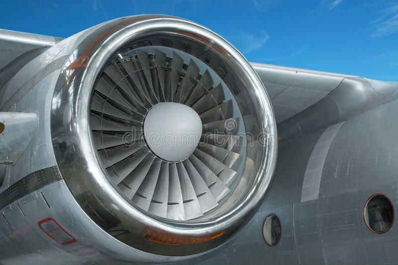 Jet engine on airplane. Wing against blue sky stock photography
