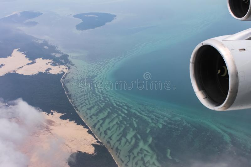 Jet engine nacelle and thruster of airplane flying out over the ocean away from land with snowcovered mountians. A Jet engine nacelle and thruster of airplane stock photography