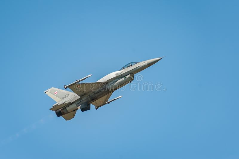 Jet fighter plane flies and shows a performance at the airshow in the clear blue sky stock image