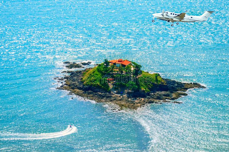 Jet flies above a small island in the sea royalty free stock photos