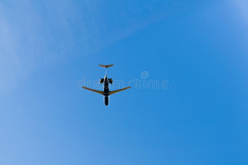 Jet flying overhead in blue skies stock photo