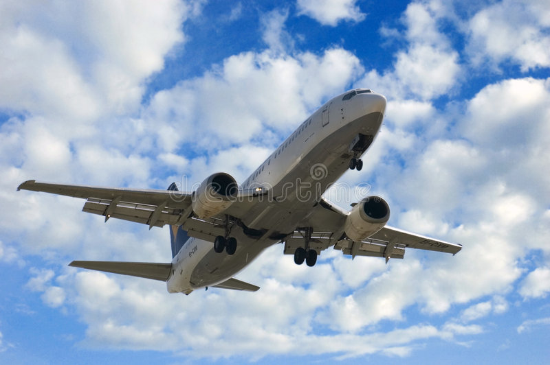 JET LANDING, CLOUD BACKGROUND royalty free stock photography