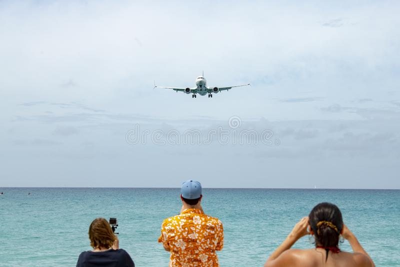 Jet landing at Maho Beach in St. Maarten royalty free stock image