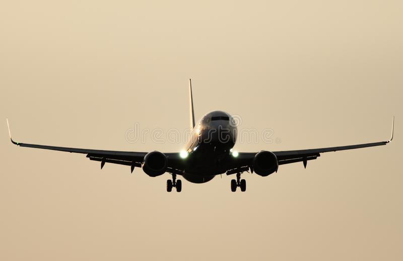 Jet plane landing against clear sky at dusk royalty free stock photography