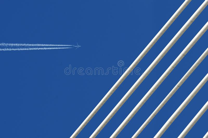 Jet plane with trace & white bridge on blue sky. The jet plane with trace & white ropes of the modern bridge is on the blue sky background. The picture can royalty free stock images