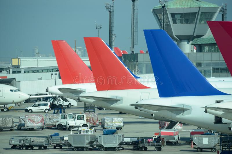 Line of parked colorful jet planes. Busy airport. stock images