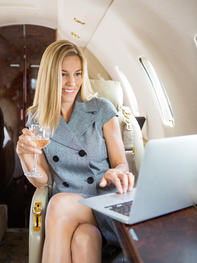 Jet privé d'Using Laptop In de femme d'affaires photographie stock libre de droits