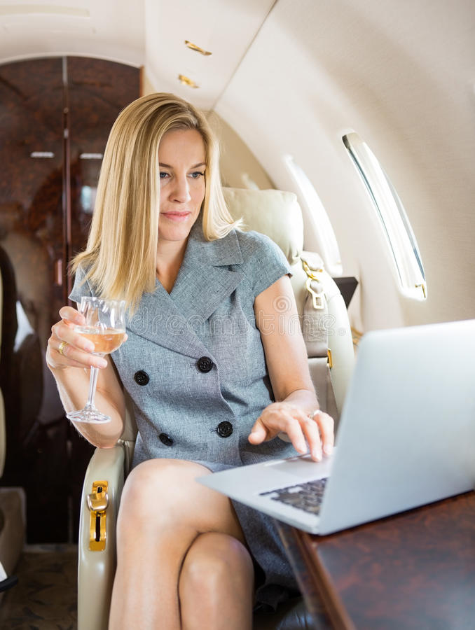 Jet privé d'Using Laptop In de femme d'affaires photo stock