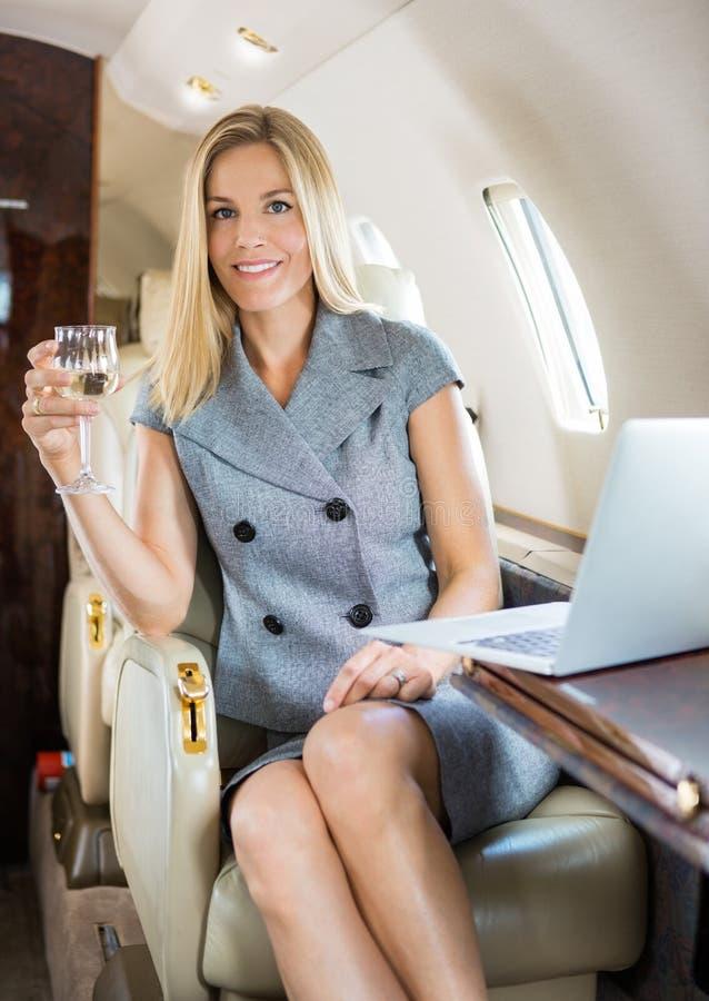 Jet privé de Holding Wineglass In de femme d'affaires images libres de droits