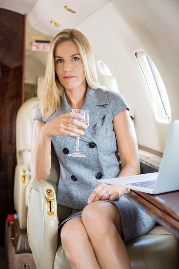 Jet privé de Holding Wineglass In de femme d'affaires image libre de droits