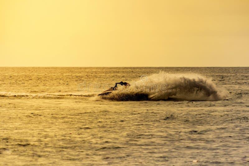 Jet ski di stile libero dell'azionamento dell'uomo al tramonto di estate fotografia stock libera da diritti