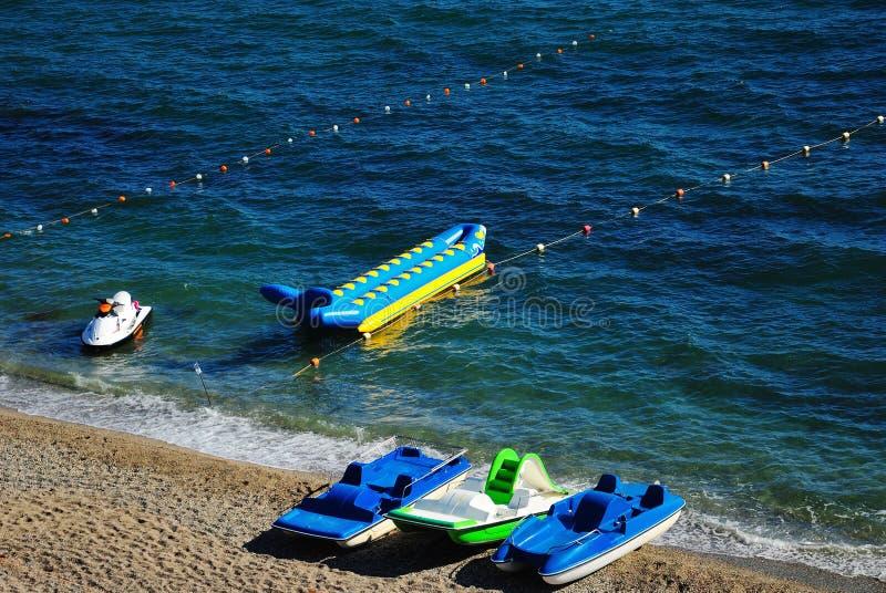 Jet-Ski- und -bananenboote und Katamaran auf dem Strand stockfotos