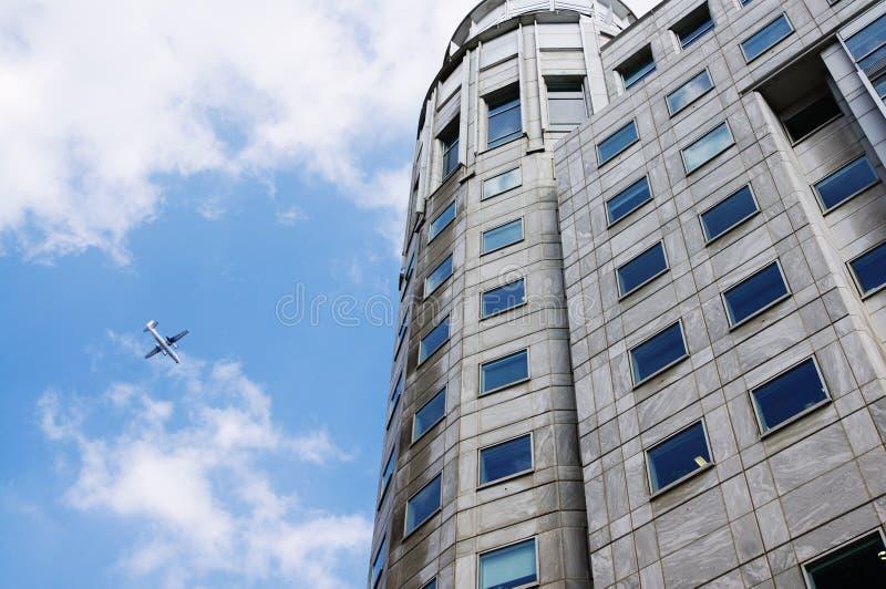 Jet som lågt flyger över kommersiell kontorsbyggnad royaltyfri foto