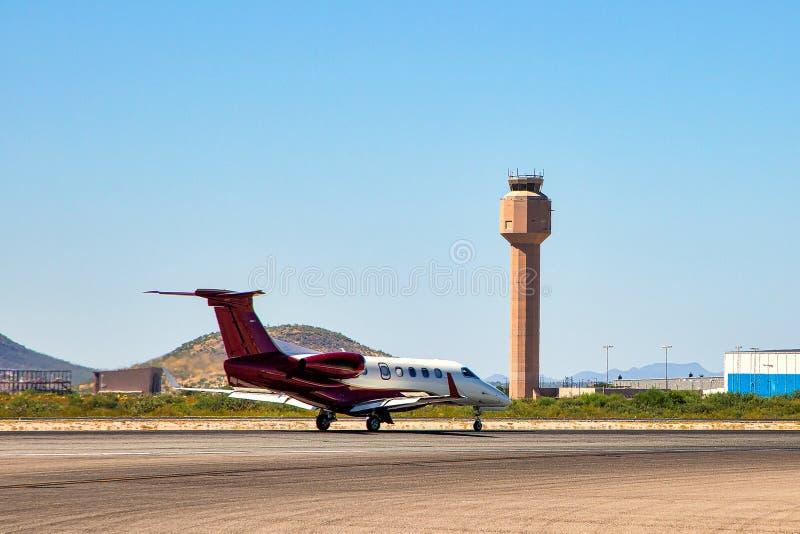 Jet su Taxiway sotto torre di controllo immagini stock libere da diritti