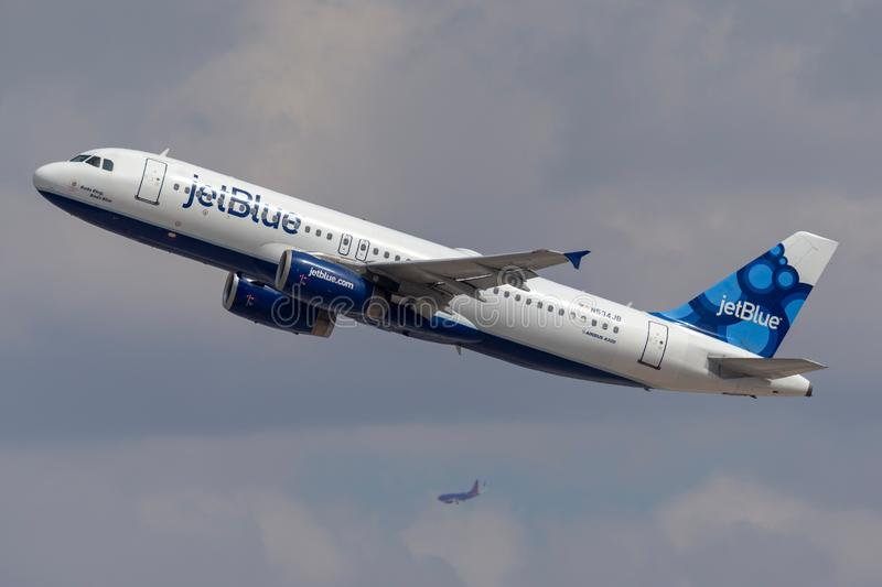 JetBlue Airways Airbus A320 aircraft taking off from McCarran International Airport Las Vegas with the air traffic control tower i stock photo