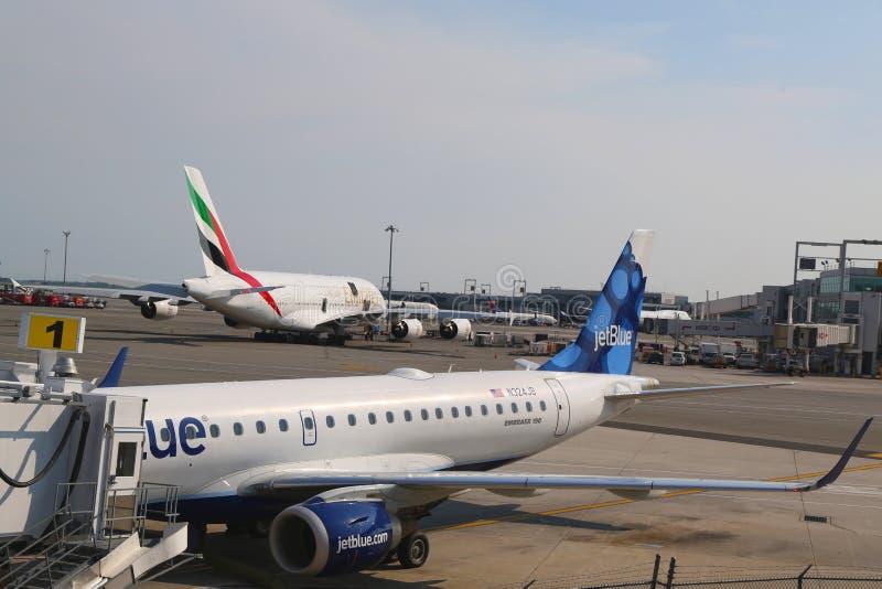 JetBlue Embraer 190 aviones en la puerta en el terminal 5 y la línea aérea Airbus A380 de los emiratos en el aeropuerto internaci imagenes de archivo