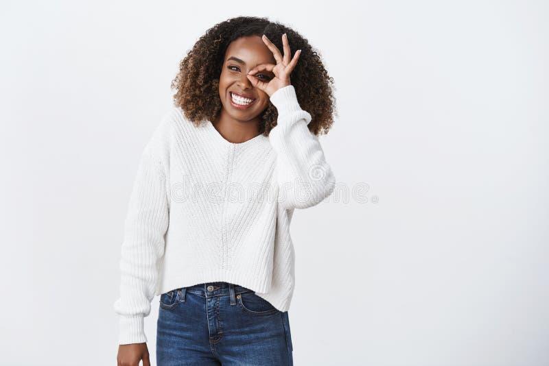 Jeter un coup d'oeil le bon côté Le chandail blanc de charme de femme à la peau foncée insouciante avec plaisir, jeans montrent c photos libres de droits