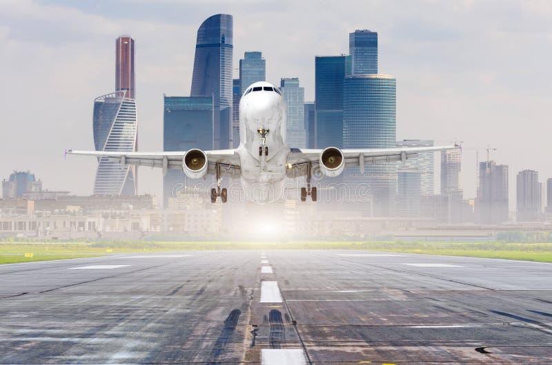 Jetflygplan för kommersiellt flygplan som att närma sig för att landa på landningsbanan, modern stad på bakgrund arkivbild