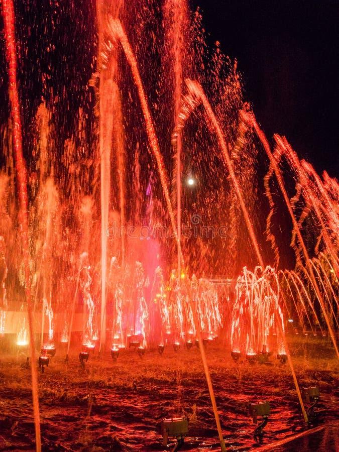 Jets d'eau colorés dans la fontaine la nuit avec la pleine lune photos stock