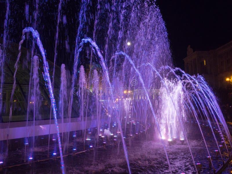 Jets d'eau colorés dans la fontaine la nuit avec la pleine lune images stock