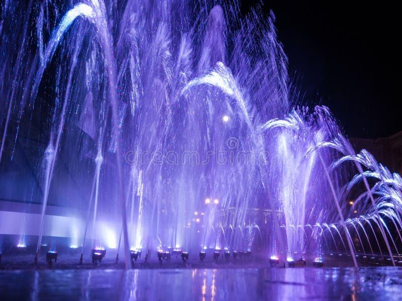 Jets d'eau colorés dans la fontaine la nuit avec la pleine lune photographie stock libre de droits