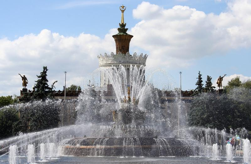 Jets of fountain in Moscow park. Against white clouds stock images