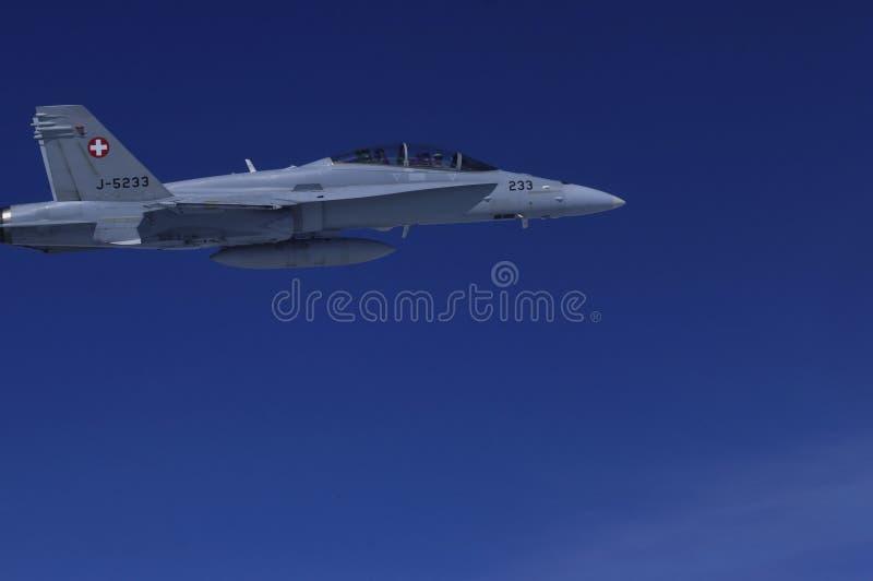 Jets militares FA-18 de la fuerza aérea suiza que escolta el airplain civil foto de archivo