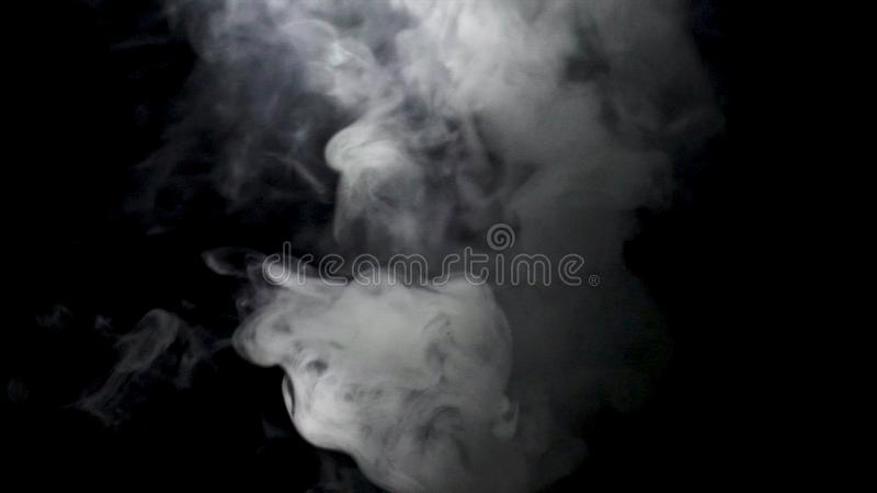 Jets of white smoke on black background. Action. Cloud of white smoke rises on black background and evaporates.  stock photo