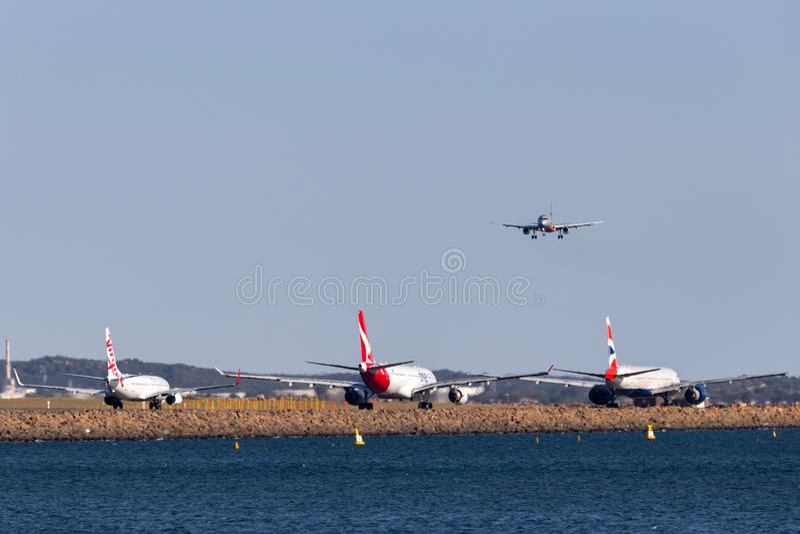 Jetstar Airbus A320 auf der Annäherung, zum bei Sydney Airport mit einer Jungfrau Boeing 737, Qantas Airbus A330 und British Airw lizenzfreie stockfotografie