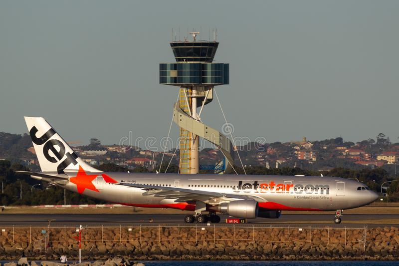 Jetstar Airways Airbus A330 aircraft taxis past the air traffic control tower at Sydney Airport stock image