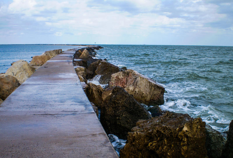 Jetti walking out into the Ocean at the Gulf of Mexico. Long Jetti extended into the ocean with waves crashing along the rocks and a long path or walkway is stock photo
