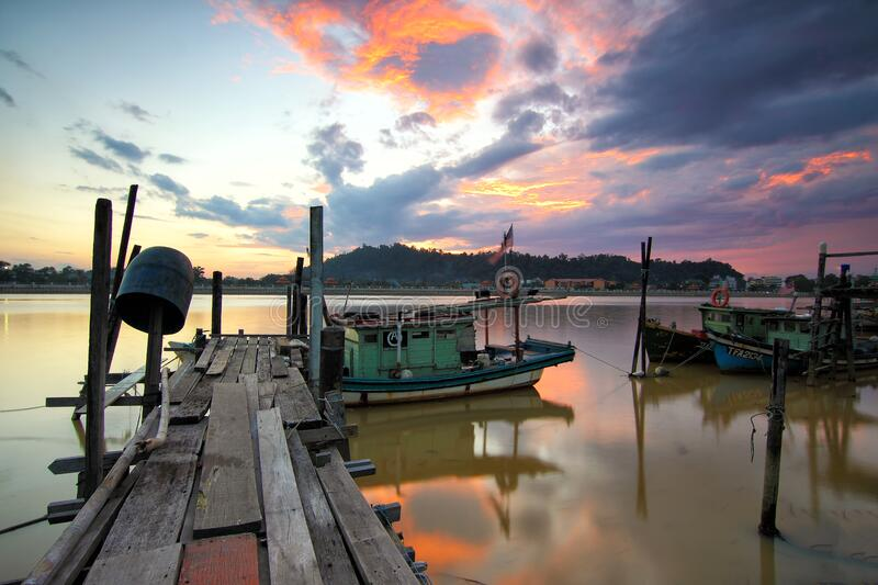 Jetty with boats at sunset royalty free stock photos