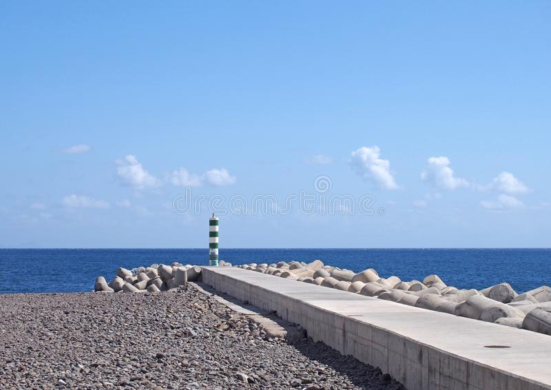 Jetty and breakwater with lighthouse on the beach in funchal madeira with bright sunlit sea and sky stock image