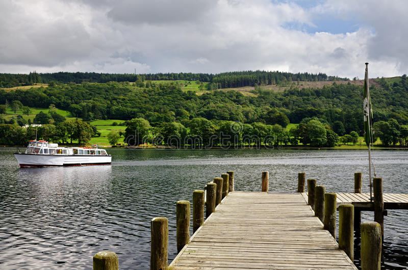 Jetty on Coniston Water. View of a boat passing a jetty on Coniston Water in the English Lake District, Cumbria royalty free stock image