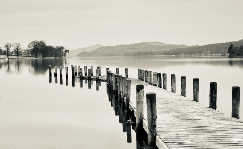 A jetty on Coniston Water. A wooden jetty looking out over Coniston Water in the Lake District Cumbria stock photography