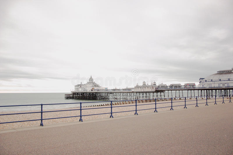 Jetty in Eastbourne, United Kingdom. A jetty with buildings on the beach in Eastbourne, United Kingdom royalty free stock image