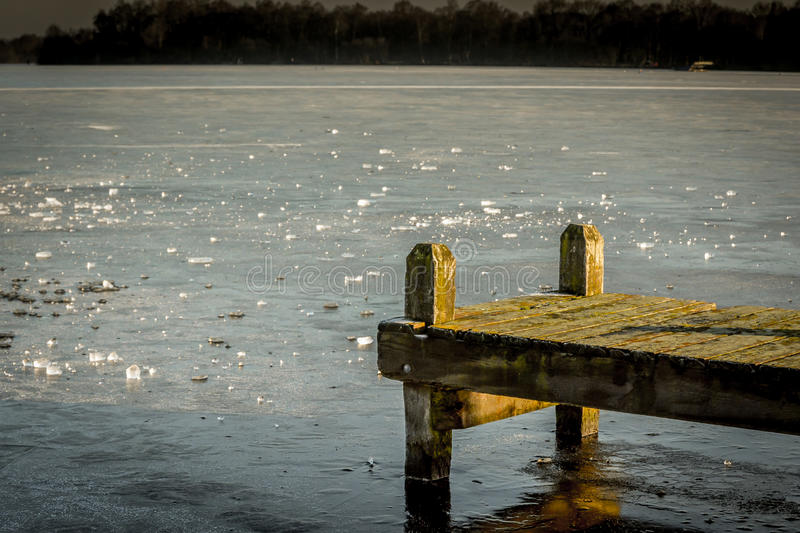 Jetty at frozen lake stock photos