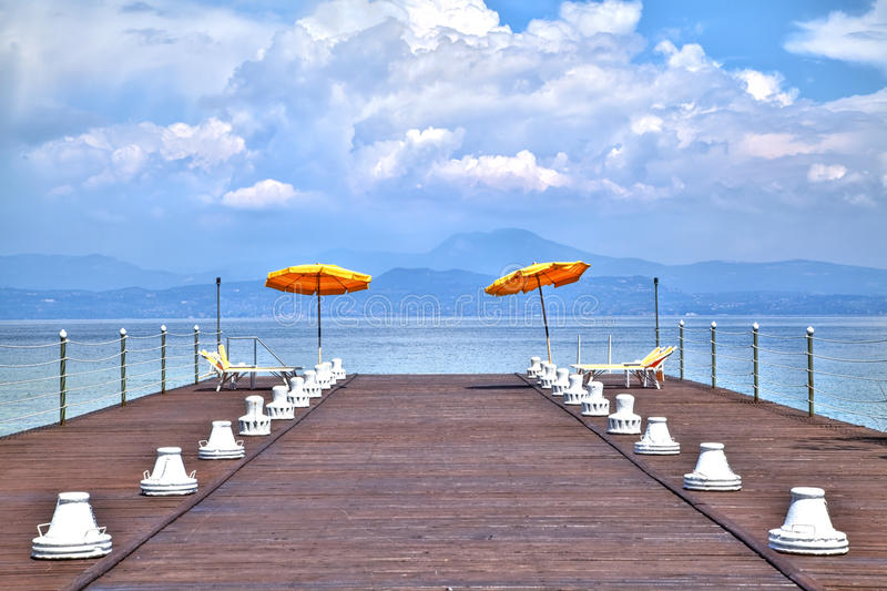 On a jetty at the Lake Garda glowing luminous orange-colored sunshades. In front of a dreamful scenic stock photography