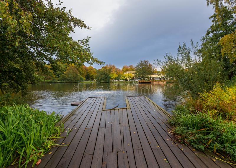 Jetty leading into lake covered with colorful trees. In slottsskogen gothenburg,Sweden royalty free stock photography