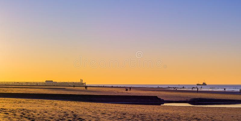 Jetty with lighthouse and a ship in the sea at sunset, the beach of blankenberge, Belgium stock photos