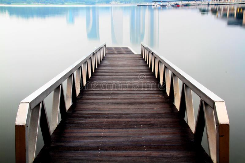 Jetty over a calmful foggy lake. royalty free stock photography