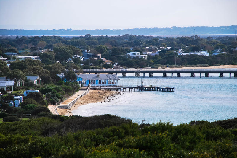 Jetty / Pier in front of the blue riverside building. At the Heads, Barwon Heads, Victoria, Australia. Birdge to Ocean Grove at the background. Houses and lots royalty free stock photos